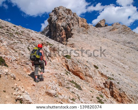 climbers are ascending the mountain via ferrata, Italy, Dolomites - stock photo