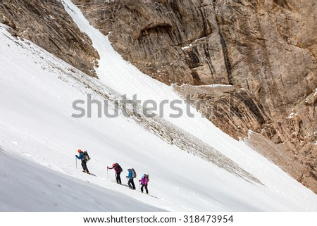 Climbers Ascending Glacier Members of Alpine Expedition Hardly Walking Up on Steep Snowfield Using Ice Climbing and Hiking Gear - stock photo