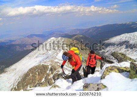 Climbers ascending snow covered mountain summit in sunny day - stock photo