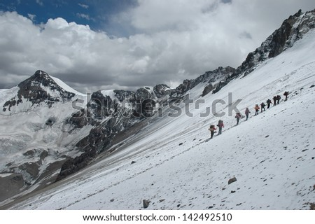 Climbers climbing Aconcagua peak in winter onditions, South America