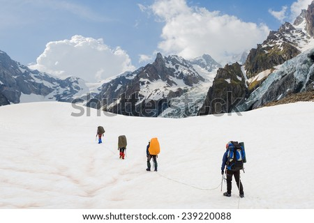 Climbers go up on the glacier with beautiful mountain landscape - stock photo