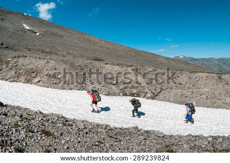 Climbers hiking in mountain, stepping on snow in line, summer season - stock photo