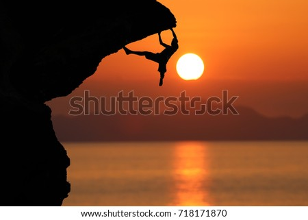 Climbers on a cliff and the sea with red sky sunset background.