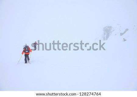 Climbers on skies and ascending a snow covered mountain slope in bad weather