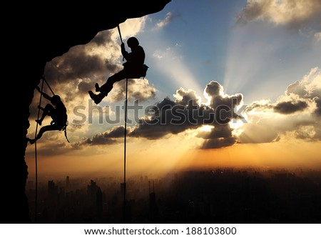 climbers on sunset background - stock photo