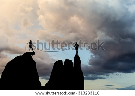 Climbers on the edge of a challenging cliff with storm clouds approaching. - stock photo