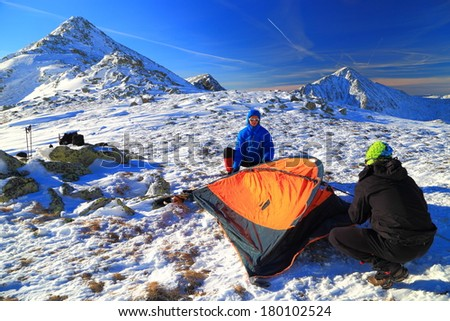 Climbers setting the tent on a snow field on the mountain