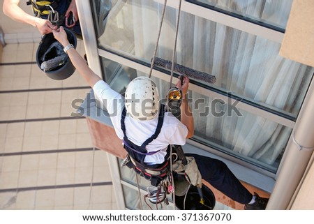 Climbers Washing Windows - Teamwork. Glass Cleaning Services. Workers hanging on climbing ropes and working together. Window and Facade Cleaning. - stock photo