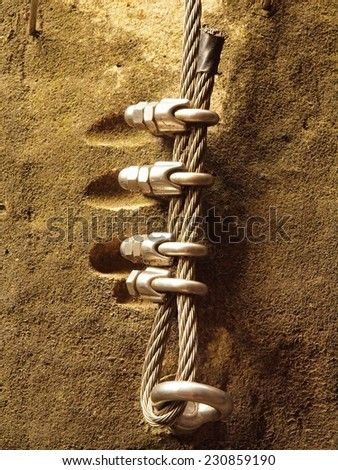 Climbers way. Iron twisted rope fixed in block by screws snap hooks. The rope end anchored into sandstone rock.  - stock photo