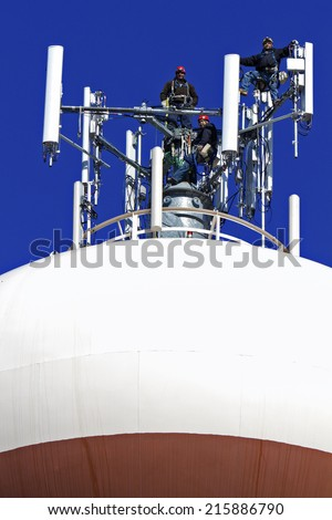 Climbers working with the cell phone antennas on the top of the water tower - stock photo