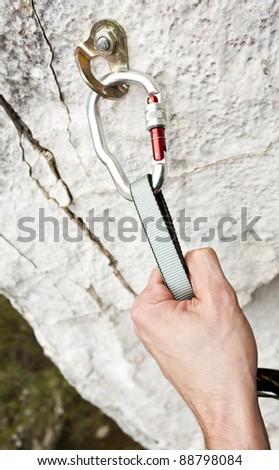 Climbing carabiner on rock wall - stock photo