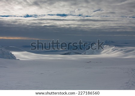 Climbing expedition on Mount Vinson, Sentinel Range, Ellsworth Mountains, Antarctica. View over the climbers in the base camp, dramatic skies in the background. Vinson is one of the 7 Summits. - stock photo