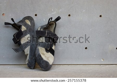 Climbing Shoes Standing Straight Up Against Climbing Wall in Climbing Gym