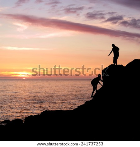 Climbing silhouette at rocky seashore gets a helping hand to get up during sunset in Brittany, France