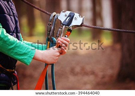 Climbing Sports Image Of A Carabiner On A Metal Rope In A Forest - stock photo