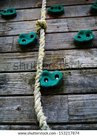 Climbing the Corporate Ladder Concept.  A rope on a climbing wall represents hard work and motivation to achieve success.  - stock photo