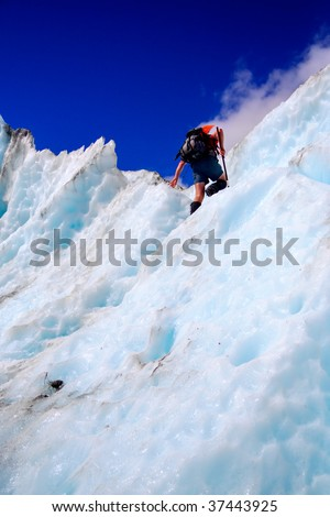 climbing the wall of a crevasse in the Franz-Joseph glacier, South Island, New Zealand