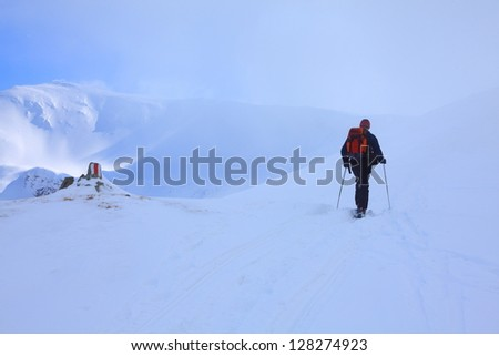 Climbing through the clouds the snowy mountain on ski during winter