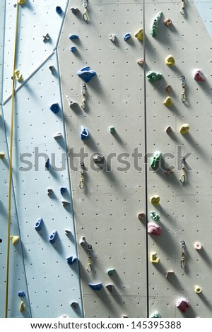 Climbing wall background with ropes and holds. - stock photo