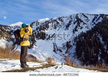 Climbing young adult looking through binoculars. Aerial view of mountain and blue sky