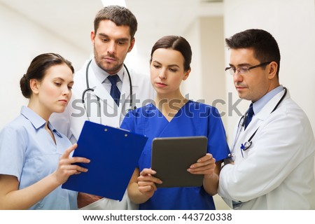 clinic, people, healthcare and medicine concept - group of medics or doctors with clipboard and tablet pc computer at hospital corridor - stock photo