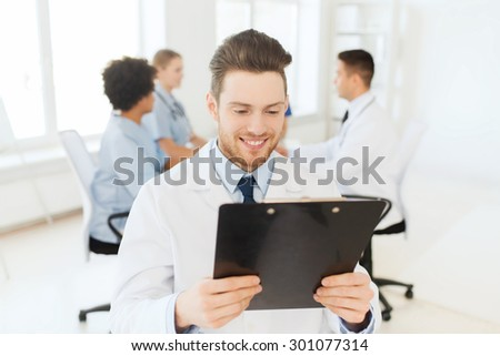clinic, profession, people and medicine concept - happy male doctor with tablet pc computer over group of medics meeting at hospital