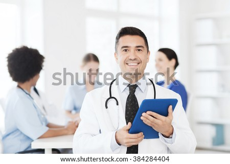 clinic, profession, people and medicine concept - happy male doctor with tablet pc computer over group of medics meeting at hospital - stock photo