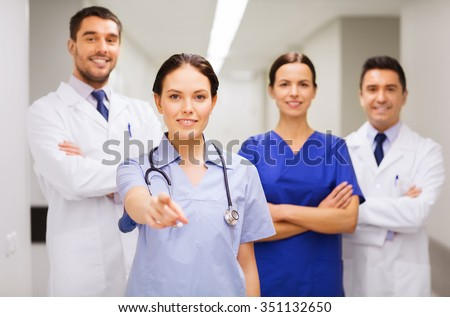 clinic, profession, people, health care and medicine concept - group of happy medics or doctors pointing finger on you at hospital corridor - stock photo