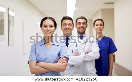 clinic, profession, people, health care and medicine concept - group of happy medics or doctors at hospital corridor - stock photo