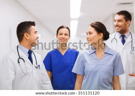 clinic, profession, people, health care and medicine concept - happy group of medics or doctors at hospital corridor - stock photo