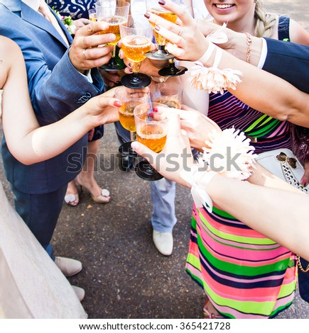 Clinking glasses with white wine and toasting. - stock photo