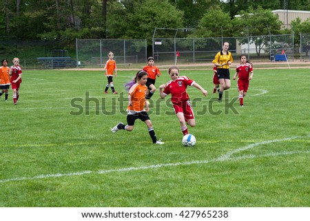 Clinton, CT, USA - May 21st., 2016: Daytime scene of young girls playing soccer in an all girls team on May 21st, 2016. The game is an organized youth soccer game.
