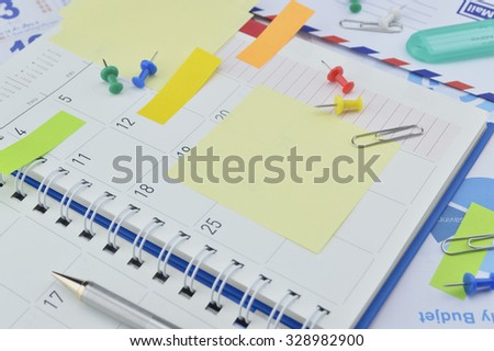 Clip with colorful sticky notes, pen and pin on business diary page - stock photo