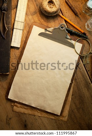 Clipboard and blank paper under incandescent light, with vintage feeling.