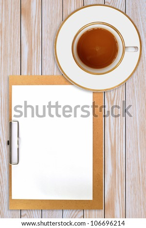 clipboard and cup of coffee on wooden background - stock photo