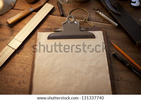 Clipboard and old parchment like blank paper under incandescent light, with vintage feeling. - stock photo