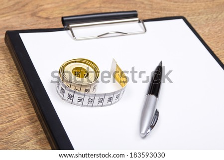 clipboard, pen and measure tape on wooden table - stock photo