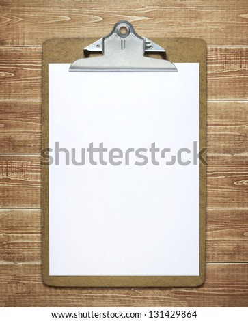 Clipboard with a blank sheet of paper on wooden table - stock photo
