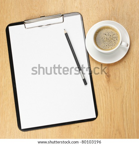 Clipboard with blank page and cup of coffee on wooden desk. View from above.