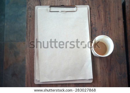 Clipboard with blank page and cup of coffee on wooden desk,Work at coffee shop.Photo in vintage style  - stock photo