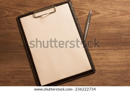 Clipboard with Blank Paper and Blue Pen on Wooden Table. Top View of Desk with Copy space for text or image - stock photo