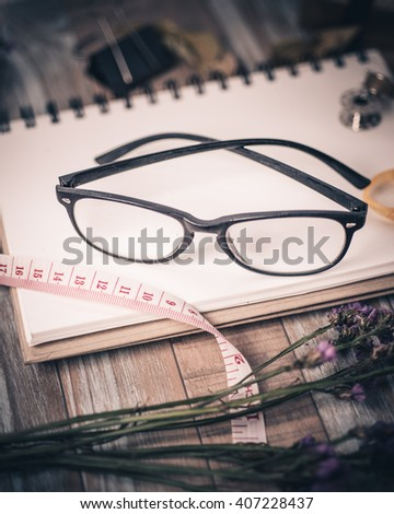 Clipboard with Blank Paper and eyeglasses on Wooden Table. Top View of Desk with Copy space for text or image
