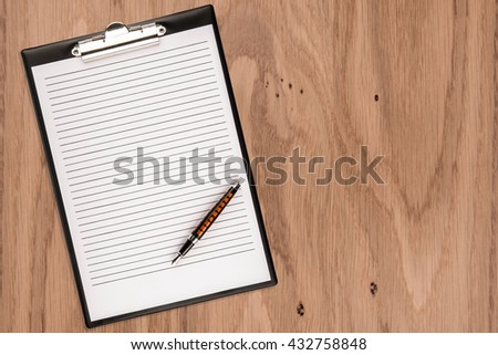 Clipboard with blank paper and pen on wooden desk. Copy space for text - stock photo