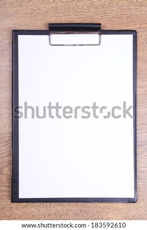 clipboard with blank sheet of paper on wooden table - stock photo