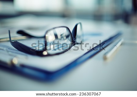 Clipboard with document, pen and eyeglasses