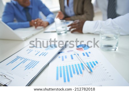 Clipboards, glass of water and pen at workplace in working environment - stock photo