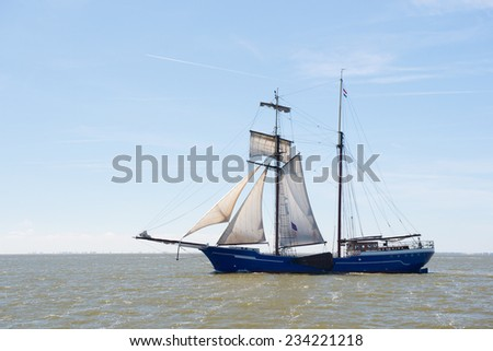 Clipper with sails on Dutch wadden sea