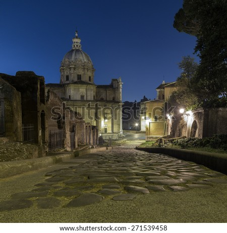 Clivo Argentario road and Santi Luca e Martina at night. Cobbled streets can be seen. - stock photo
