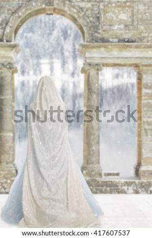 cloaked woman by castle lake