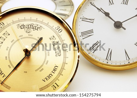 Clock and barometer dials or bezels focus on barometer face - stock photo